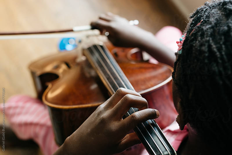 Top view of a black girl playing cello by Gabriel (Gabi) Bucataru for Stocksy United