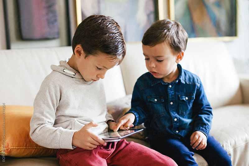 Two little brothers playing together with their digital tablet at home. by BONNINSTUDIO for Stocksy United