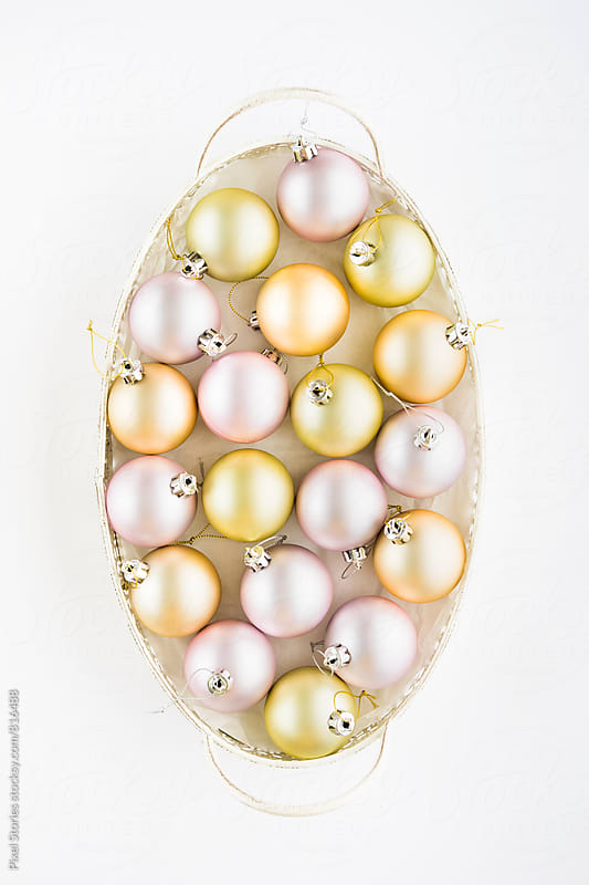 Pastel Christmas baubles in a white tray by Pixel Stories for Stocksy United