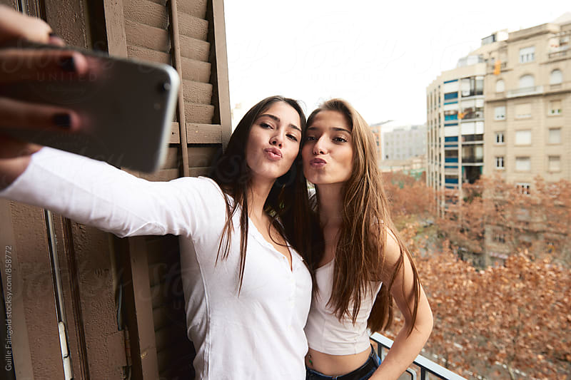 Two girlfriends taking selfie on balcony by Guille Faingold for Stocksy United