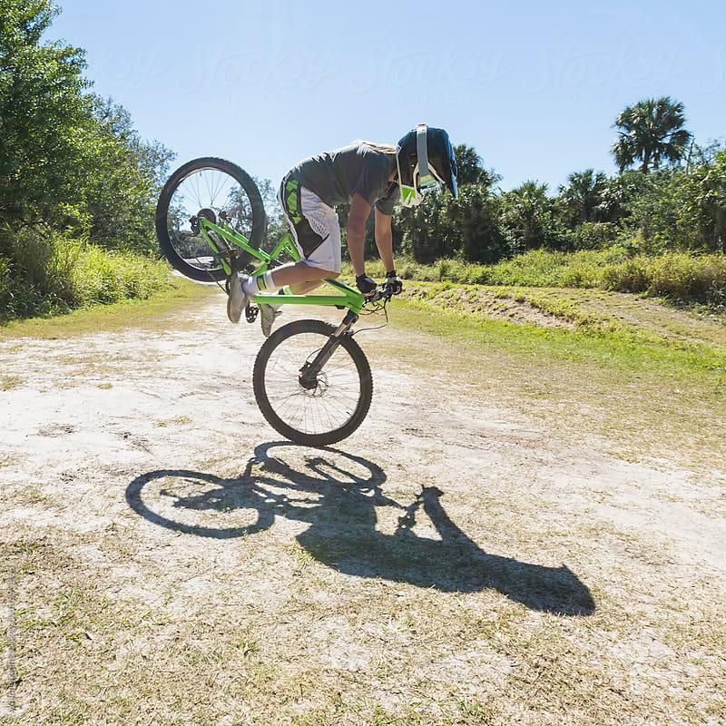 Mountain biker up on front wheel by Adam Nixon for Stocksy United