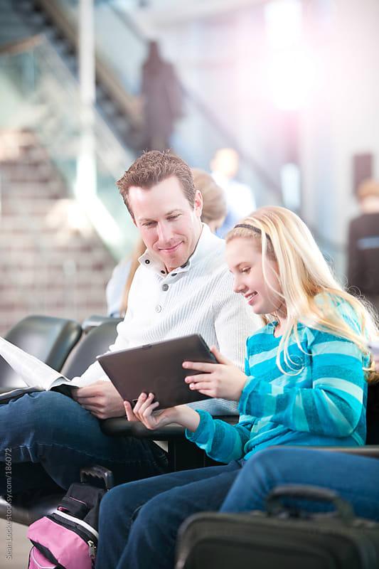 Airport: Girl Shows Dad Digital Tablet by Sean Locke for Stocksy United