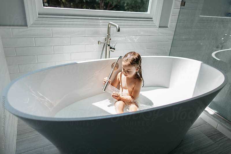 A beautiful young girl washing herself in a large bathtub by Jakob for Stocksy United