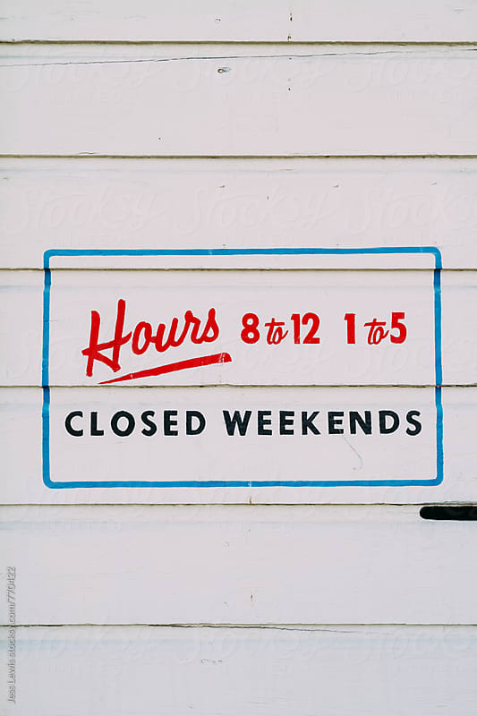 hand lettered sign showing business hours by Jess Lewis for Stocksy United
