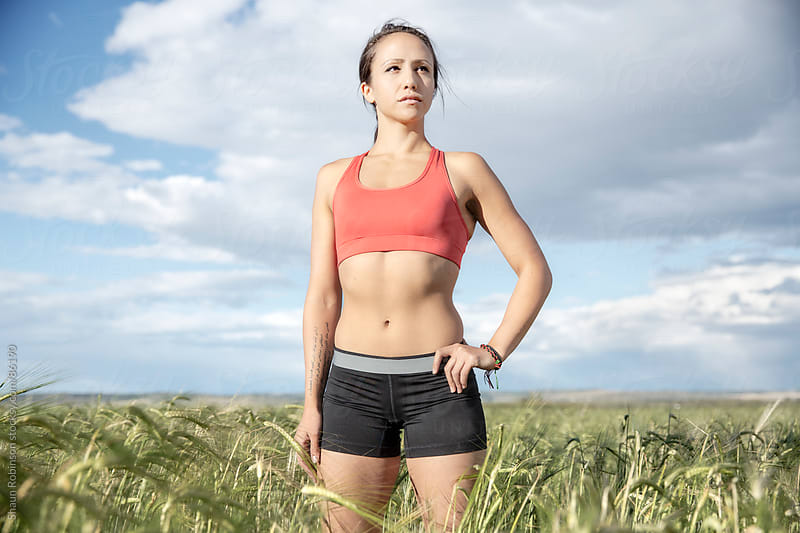 Young fit woman standing in a wheat field in workout clothes by Shaun Robinson for Stocksy United