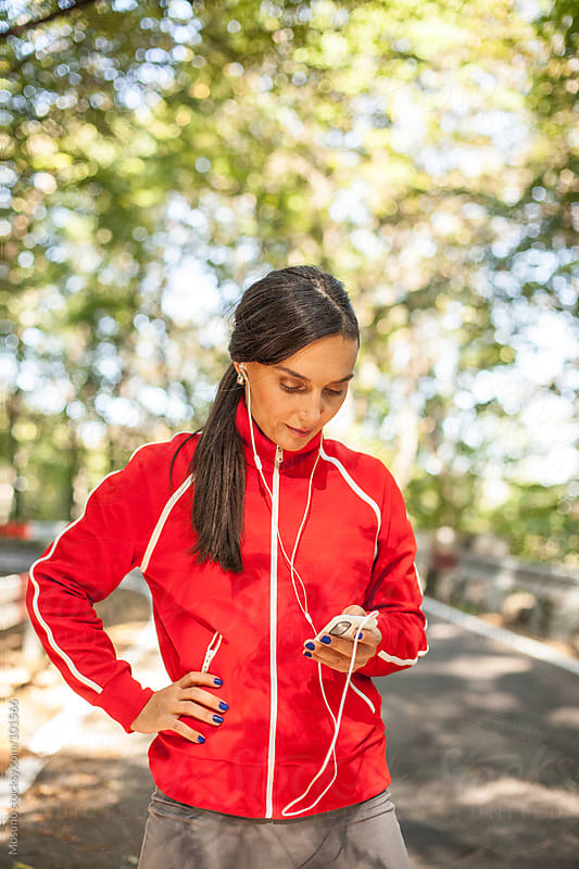 Woman Preparing Music for Jogging by Mosuno for Stocksy United
