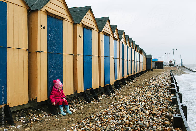 Little girl wearing a pink jacket sits outside a row of beach huts in winter. by Julia Forsman for Stocksy United