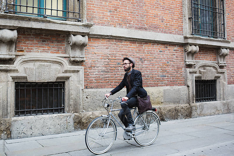 Young man riding his bike in the city center by michela ravasio for Stocksy United