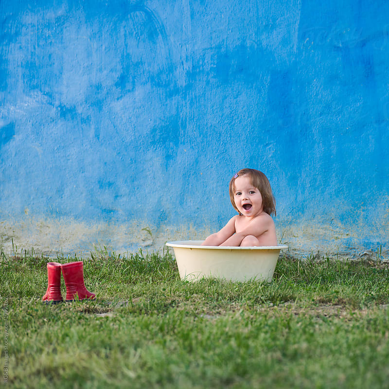 Toddler girl cooling down bathing in a plastic basin outdoor by RG&B Images for Stocksy United