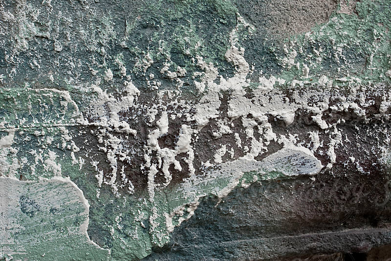 closeup of patterns of paint peeling texture on bricks in urban landscape by Ron Mellott for Stocksy United
