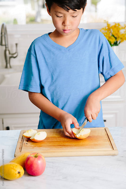 Young boy preparing a healthy fruit snack by Curtis Kim for Stocksy United