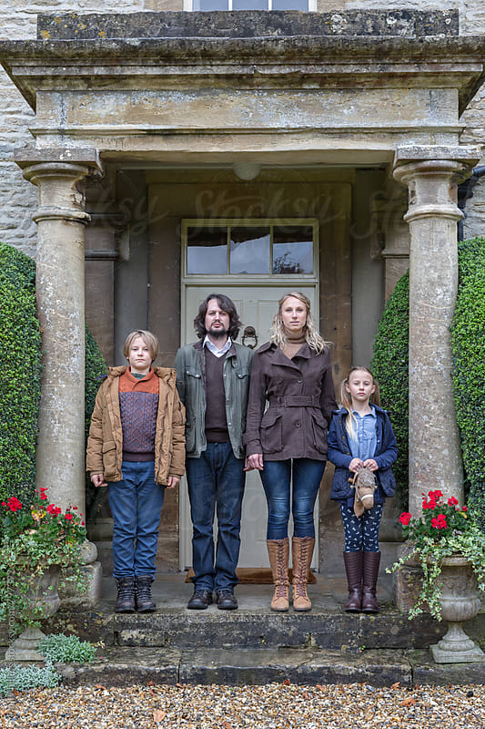 Young family at the entrance to their house looking directly at camera. Slightly snooty by Paul Phillips for Stocksy United
