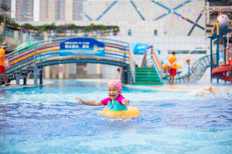 happy little asian girl in swimming pool by Bo Bo for Stocksy United