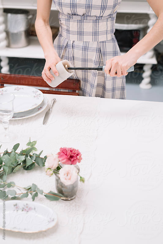 Young woman setting a table for dinning by Alberto Bogo for Stocksy United