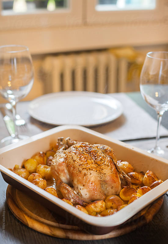 Roast chicken with potatoes by Davide Illini for Stocksy United