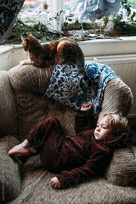 Small blonde child wearing cuddly brown onesie relaxes on an armchair with her cat. by Julia Forsman for Stocksy United