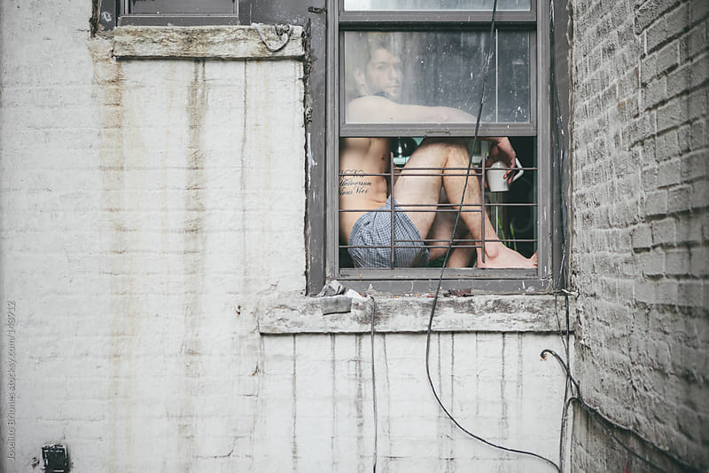 Shirtless Man in Boxer Shorts Drinking Coffee Sitting at Window of Urban Apartment by Joselito Briones for Stocksy United