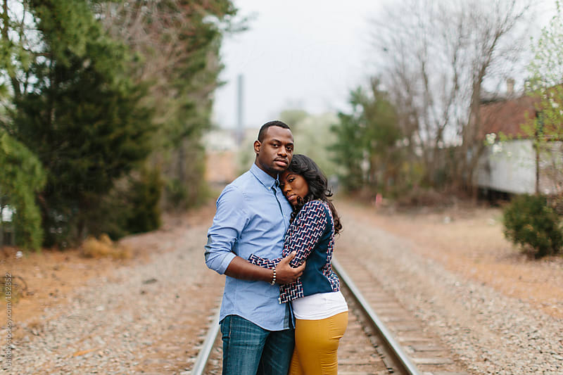 Trendy and stylish African-American embracing on train tracks by Jakob for Stocksy United