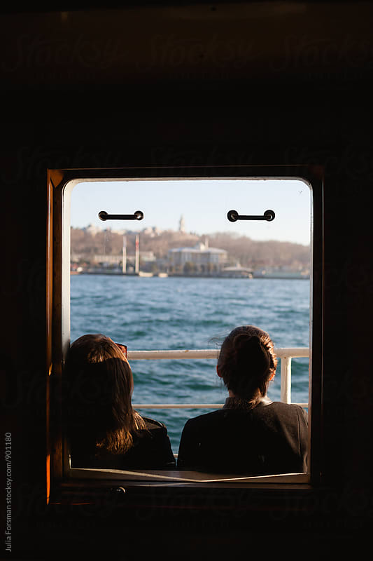 Two women friends seen from behind through a ferryboat window on the Bosphorus. by Julia Forsman for Stocksy United