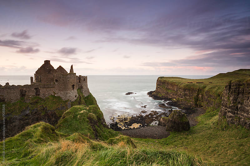 Ruins of an Irish castle beside the sea at sunset by Marilar Irastorza for Stocksy United