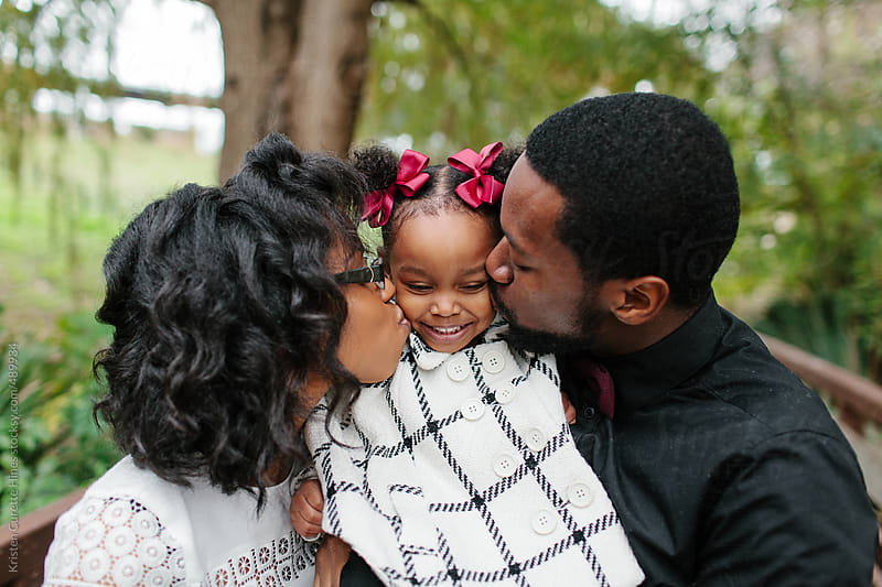 Parents showing affection to their little girl by Kristen Curette Hines for Stocksy United