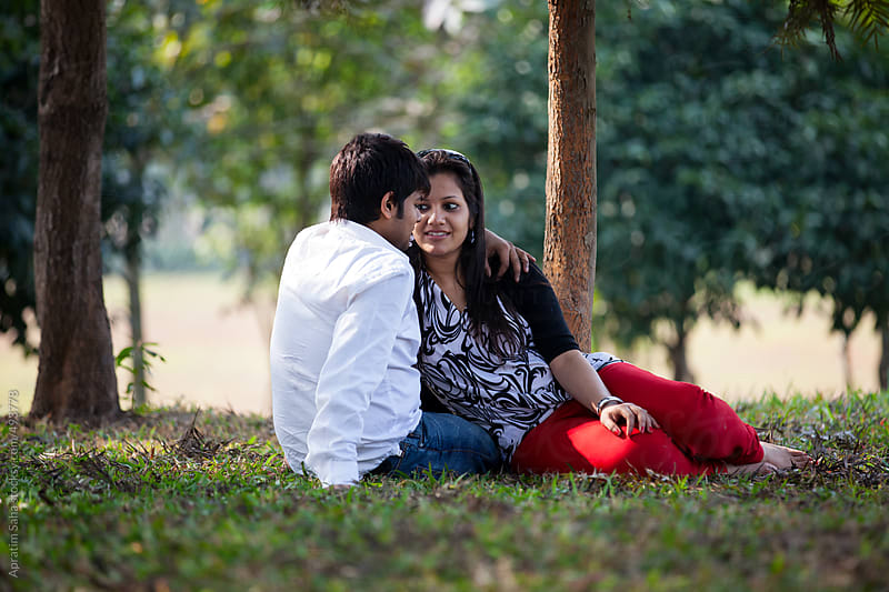 A young couple enjoying an intimate moment in the park by Apratim Saha for Stocksy United