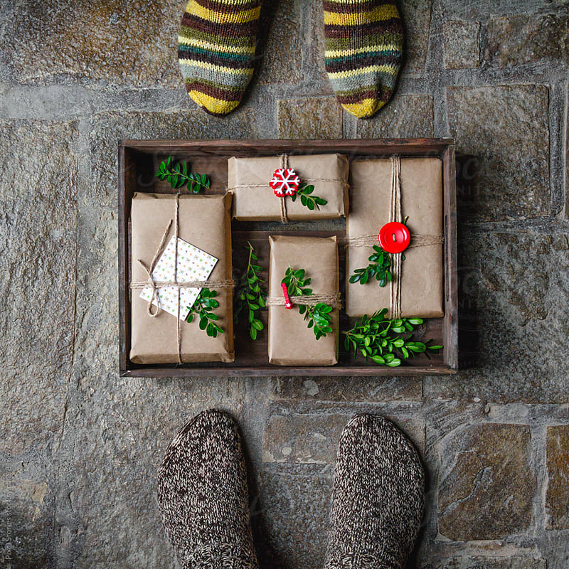 Feet with warm winter socks standing in front of Christmas gifts by Pixel Stories for Stocksy United
