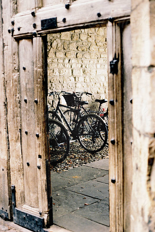 Cycles seen through an open gate by Helen Rushbrook for Stocksy United