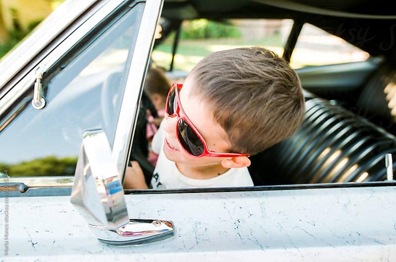 boy drives classic car by Maria Manco for Stocksy United