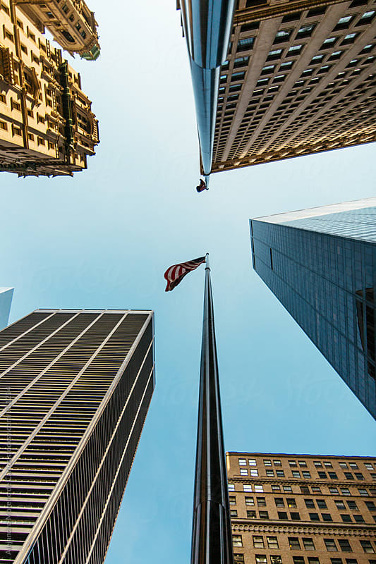 Low angle view of skyscrappers in New York City with american flag by Alejandro Moreno de Carlos for Stocksy United