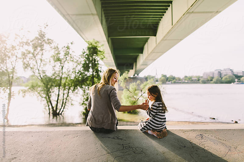 Mother and her little daughter sitting under the bridge  by Evgenij Yulkin for Stocksy United