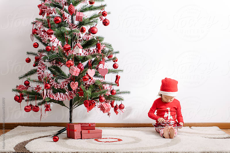 Toddler girl using digital PC by christmas tree by Maa Hoo for Stocksy United
