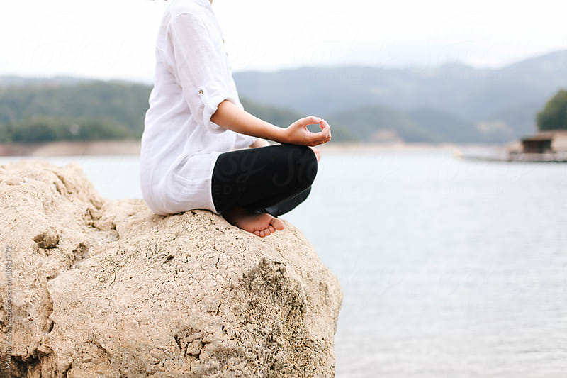 Female person meditating, sitting on a rock by Marija Kovac for Stocksy United