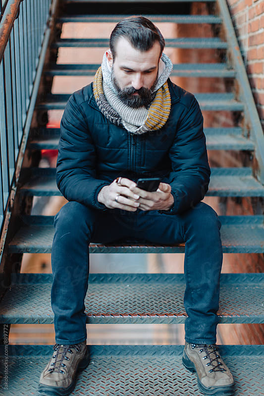 Handsome well groomed man sitting using his phone while sitting on stairs by Jakob for Stocksy United