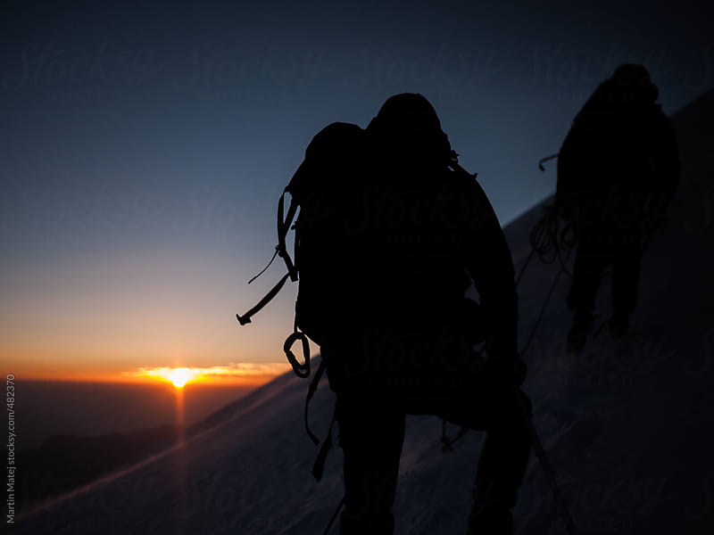 Mountaineers silhouettes with sunrise in the backgound by Martin Matej for Stocksy United
