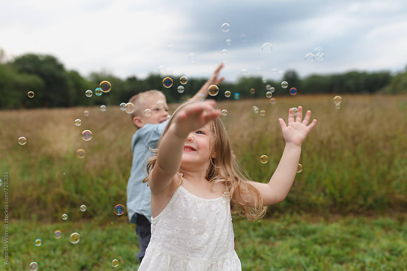 A girl pops bubbles, brother in background by Amanda Worrall for Stocksy United