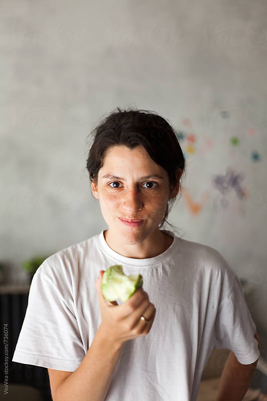Beautiful young woman eating an apple indoor by VeaVea for Stocksy United