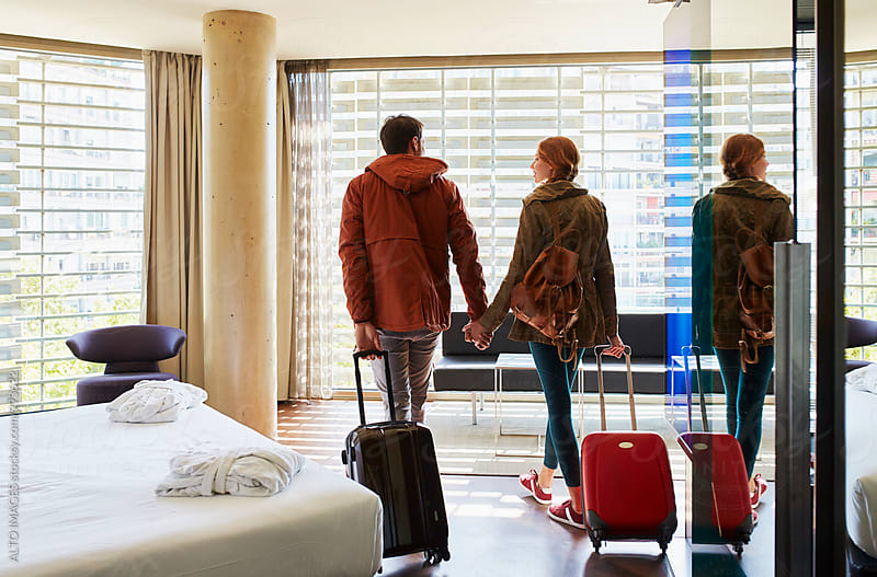 Loving Couple With Luggage Entering In Hotel Room by ALTO IMAGES for Stocksy United
