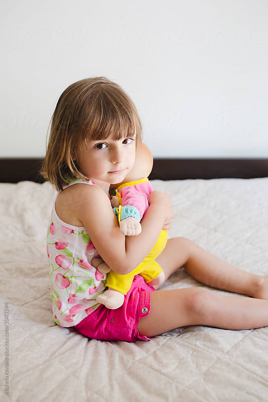 Portrait of cute little girl with her doll by michela ravasio for Stocksy United