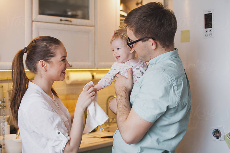 Happy family of three on their kitchen by Irina Efremova for Stocksy United