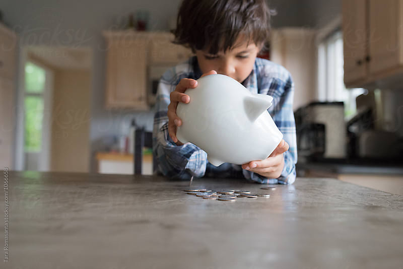 child shakes coins out of piggy bank by Tara Romasanta for Stocksy United