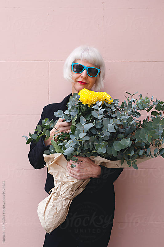 Trendy and attractive older female holding a bunch of colourful flowers by Natalie JEFFCOTT for Stocksy United