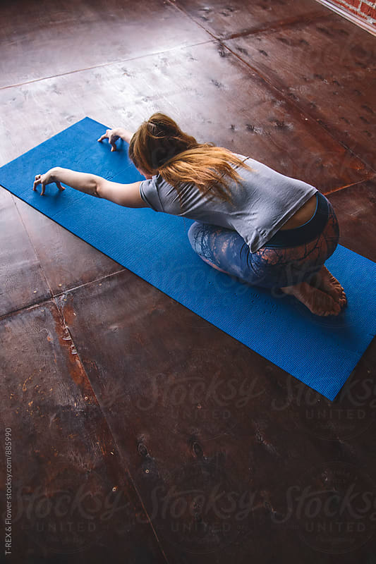 Close-up of woman stretching in yoga studio by Danil Nevsky for Stocksy United