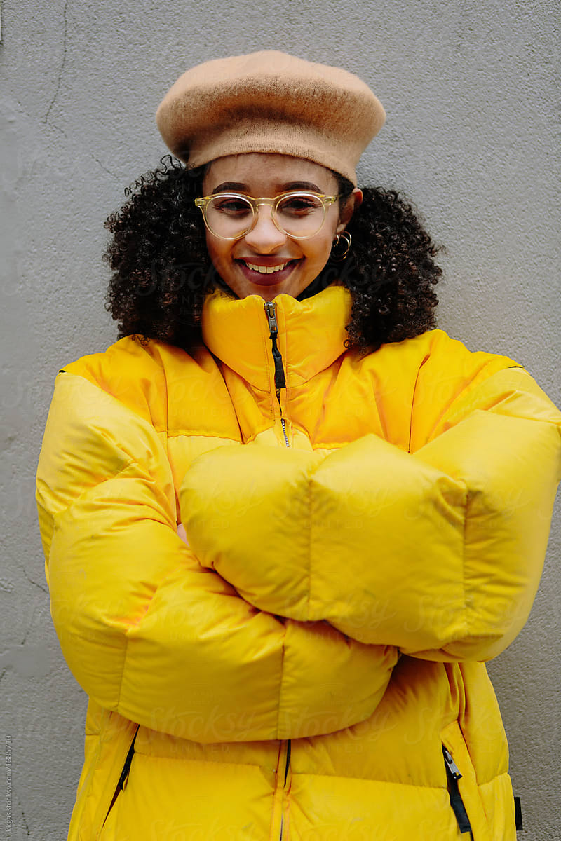 402ac827e Stock Photo - Beautiful Mixed Ethnicity Woman Wearing Thick Yellow Puffer  Jacket And Beret.
