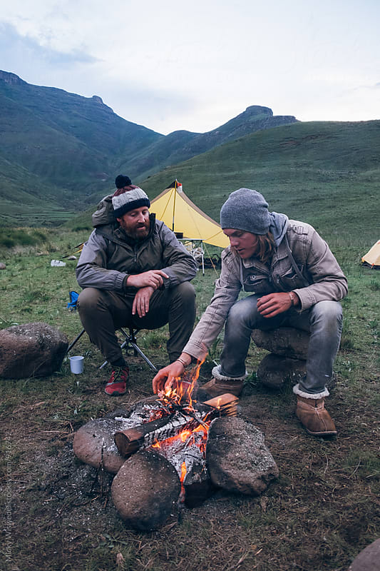 hiker outdoorsmen sitting around a campfire at dawn by Micky Wiswedel for Stocksy United