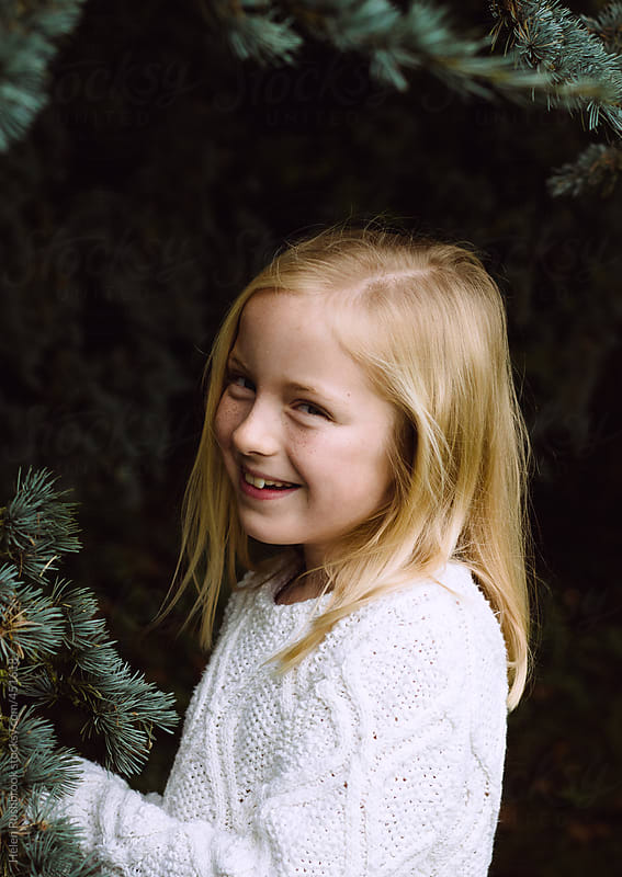 A little girl with a cheeky smile under a tree. by Helen Rushbrook for Stocksy United