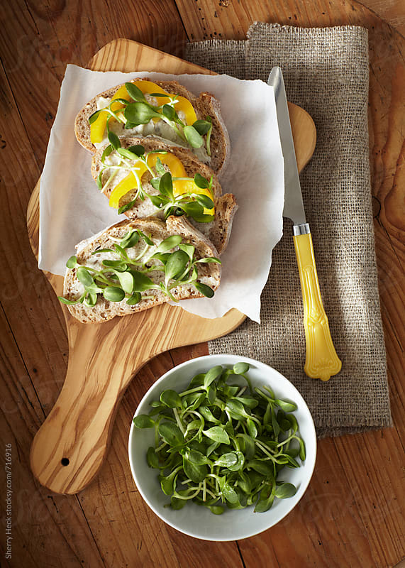 Bread with butter spread, peppers and sprouts prepared on cutting board by Sherry Heck for Stocksy United