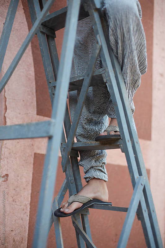 Close up of a young man on a ladder by Miquel Llonch for Stocksy United