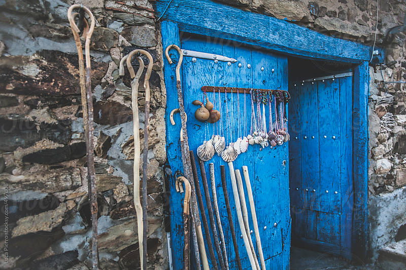 Blue door with sticks and seashells on the wall by Luca Pierro for Stocksy United
