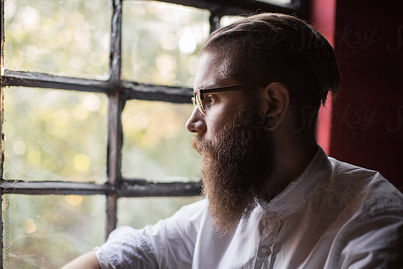 Bearded young man looking through the window by Jovo Jovanovic for Stocksy United